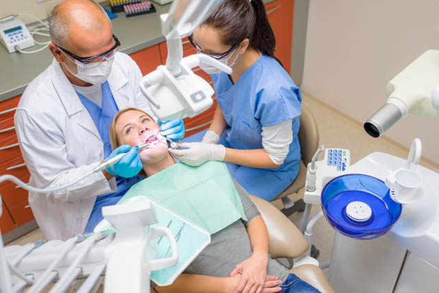 Лікар-стоматолог зліва на світлині, асистент лікаря - з правого боку, пацієнт - посередині